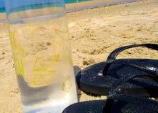 Nahaufnahme auf Wasserflasche und schwarze Flipflops auf einem Sand Lizenzfreies Stockfoto