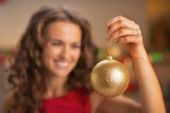 Nahaufnahme auf Weihnachtsball in der Hand der Frau im roten Kleid lizenzfreie stockbilder