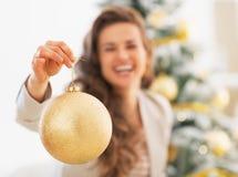 Nahaufnahme auf Weihnachtsball in der Hand der glücklichen jungen Frau Lizenzfreie Stockbilder