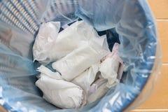 Nahaufnahme benutzte die Damenbindeauflage eingewickelt abgeschafft im Mülleimer stockbild