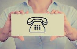 Nahaufnahme übergibt das Halten des Kartenzeichens mit Telefonkontaktikone Lizenzfreies Stockfoto