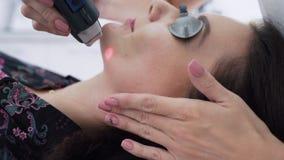 Nahaufnahme Cosmetologist macht Laser-Behandlung zum Gesicht der jungen Frau, Abbau der Akne, Zeitlupe stock video footage