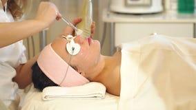 Nahaufnahme Cosmetologist wendet ein befeuchtendes Gel der B?rste auf dem Gesicht eines M?dchens an stock footage