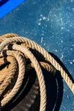 Nahaufnahme das alte ausgefranste Bootsseil auf blauem Beschaffenheitshintergrund stockfoto