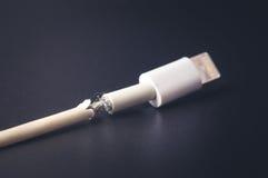 Nahaufnahme das defekte intelligente Telefon-Ladegerät-Kabel auf schwarzem Hintergrund Stockbild
