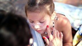 Nahaufnahme, das Kind, Mädchen, schwerer Sonnenbrand auf dem Gesicht Mutter schmiert Orte von Bränden reichlich mit einer speziel stock footage