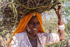 Nahaufnahme der älteren Frau mit Brennholz auf ihrem Kopf stockbild