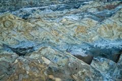 Nahaufnahme der abgefressenen Steinbeschaffenheit auf dem Strand Stockbilder