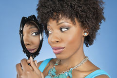 Nahaufnahme der Afroamerikanerfrau im Spiegel über farbigem Hintergrund betrachtend Stockfotos
