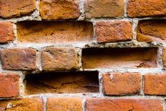 Nahaufnahme der alten schädigenden Backsteinmauer mit Löchern Lizenzfreies Stockfoto