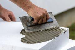 Nahaufnahme der Arbeitskrafthand mit der Kelle, die Kleber auf weißem steifem Polyurethanschaumblatt für Hausisolierung aufträgt  lizenzfreies stockbild