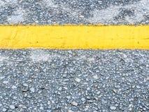 Nahaufnahme der Asphaltstraßenbeschaffenheit mit gelber Linie Stockbild