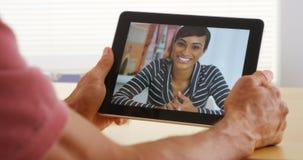 Nahaufnahme der attraktiven afrikanischen Frau, die auf Tablette spricht Lizenzfreie Stockfotografie