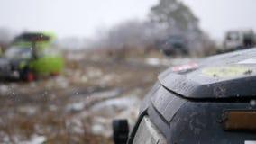 Nahaufnahme der Auto ` s Haube mit fallendem Schnee auf einem Hintergrund von Herbstlichtung, Zeitlupe stock video footage