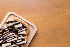 Nahaufnahme der Banane mit Schokolade auf gegrilltem Brot auf links Lizenzfreie Stockfotografie