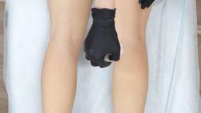 Nahaufnahme der Beine, auf denen der Kosmetiker die Haarabbaumasse schmiert und zerrei?t, auf der R?ckseite des Beines stock video
