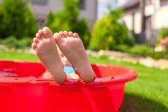 Nahaufnahme der Beine des Kleinkindes im kleinen roten Pool Lizenzfreies Stockfoto