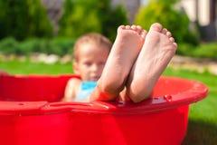 Nahaufnahme der Beine des Kleinkindes im kleinen roten Pool Stockbilder