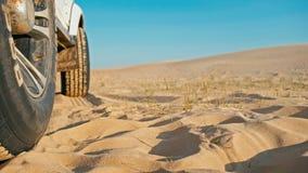 Nahaufnahme der Beine einer jungen Frau nahe bei einem Fahrzeug des Autos 4x4 den Sonnenuntergang auf einem der WüstenSanddüne ge lizenzfreies stockbild