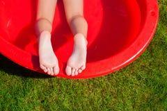 Nahaufnahme der Beine eines kleinen Mädchens im Pool Stockbild