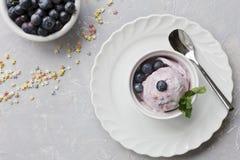 Nahaufnahme der Blaubeereiscreme und der Blaubeeren mit tadellosen Blättern in einer weißen Schüssel auf einem grauen Hintergrund Stockfotografie