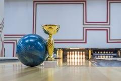 Nahaufnahme der blauen Bowlingkugel nahe goldener Trophäe Stockfotos