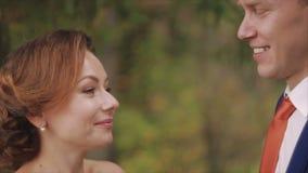 Nahaufnahme der Braut und des Bräutigams, die Eheringe über grünem Naturhintergrund austauschen stock video footage