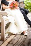 Nahaufnahme der Braut und des Bräutigams, die in einem Park sitzen Lizenzfreies Stockfoto