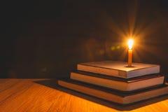 Nahaufnahme der brennenden Kerze mit Stapel des alten Buches auf hölzernem Lizenzfreies Stockfoto