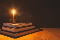 Nahaufnahme der brennenden Kerze mit Stapel des alten Buches auf Holztisch Stockbilder