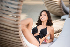 Nahaufnahme der Brunettefrau in einem schwarzen Badeanzuglügen gestützt auf ihren Händen auf einem hölzernen Ruhesessel am Luxus- lizenzfreies stockbild