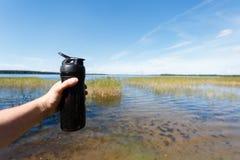 Nahaufnahme der Eignungsschüttel-apparatflasche in der Hand der Männer gegen den schönen See Trägt Snack die Frischluft zur Schau Lizenzfreies Stockbild