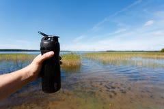 Nahaufnahme der Eignungsschüttel-apparatflasche in der Männer ` s Hand gegen den schönen See Trägt Snack die Frischluft zur Schau Lizenzfreie Stockbilder