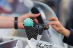 Nahaufnahme der Eiscreme in den schwarzen Waffelkegeln Hände des Kunden zahlend mit einer Kreditkarte Verkäufer, der eine Kreditk lizenzfreie stockfotografie