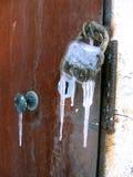 Nahaufnahme der Eisentür mit dem alten rostigen Verschluss eingefroren mit Eiszapfen stockfotos
