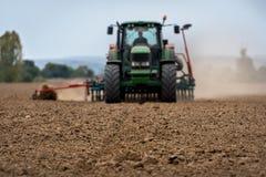 Nahaufnahme der Ernte mit pflügendem Feld des Traktors lizenzfreies stockbild