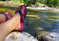 Nahaufnahme der Füße der Frau Sandalen auf Rand eines Nebenflusses tragend Stockbilder