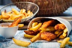 Nahaufnahme der Fische u. der Chips diente im Papier Stockbilder