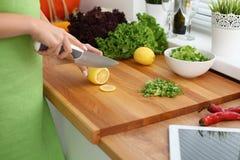Nahaufnahme der Frau übergibt das Kochen des Gemüses Salat in der Küche Hausfrau schneidet Zitrone Gesundes Mahlzeit- und Vegetar Lizenzfreies Stockfoto