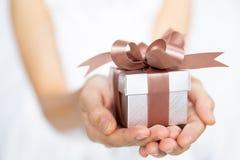 Nahaufnahme der Frau übergibt eine kleine Geschenkbox für spezielles sogar halten stockbilder