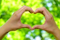Nahaufnahme der Frau übergibt das Zeigen von Herzform auf natürlichem grünem Hintergrund Stockfoto