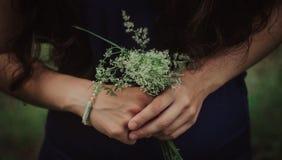 Nahaufnahme der Frau, das tragende blaue Kleid, halten im Handblumenstraußgänseblümchen blüht draußen, neues Lebenkonzept stockbilder