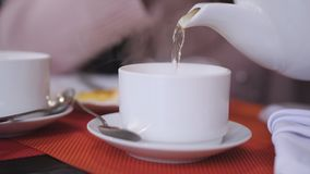Nahaufnahme der Frau heißen grünen Tee in einer weißen Schale gießend, die auf einer Tabelle im Restaurant steht stock footage