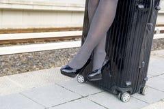 Nahaufnahme der Frau sitzend auf Koffer an der Bahnstation stockbilder