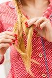 Nahaufnahme der Frau Zopf auf blondem Haar tuend Stockbilder