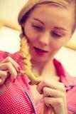 Nahaufnahme der Frau Zopf auf blondem Haar tuend Stockfoto