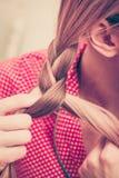 Nahaufnahme der Frau Zopf auf blondem Haar tuend Stockbild
