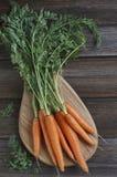 Nahaufnahme der frischen rohen Karotte auf hölzernem Brett Draufsicht über rustikalen hölzernen Hintergrund Stockfotografie