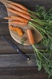 Nahaufnahme der frischen rohen Karotte auf hölzernem Brett mit Messer Draufsicht über rustikalen hölzernen Hintergrund Lizenzfreie Stockfotografie