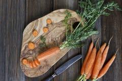 Nahaufnahme der frischen rohen Karotte auf hölzernem Brett mit Messer Draufsicht über rustikalen hölzernen Hintergrund Lizenzfreie Stockfotos